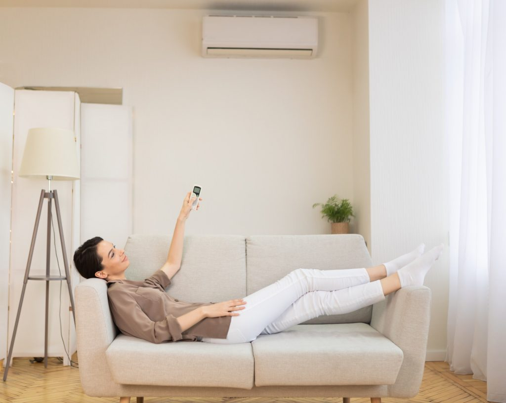 Young woman switching on air conditioning at her house